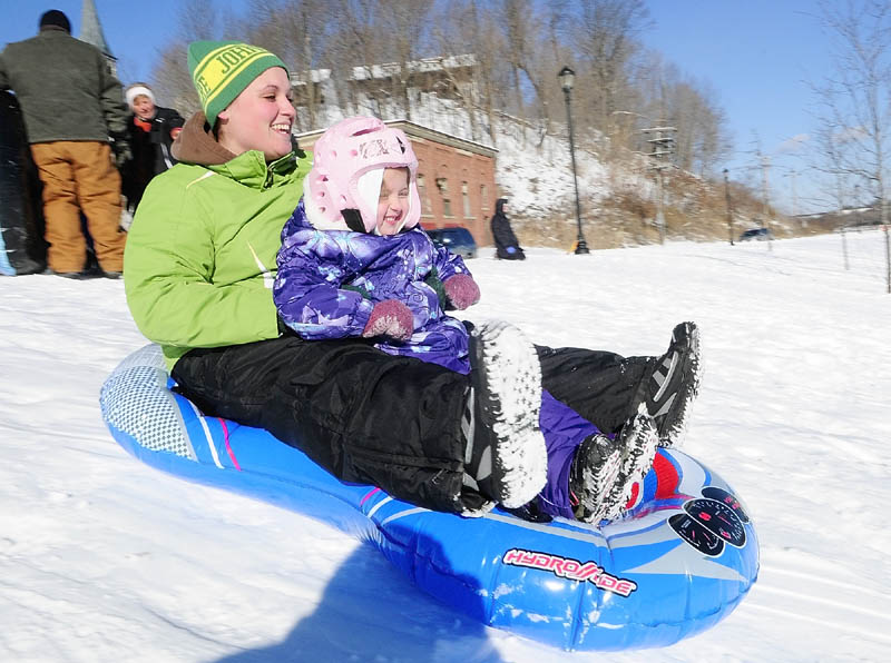 Kelsey Morin, left, and her daughter, Hadleigh Morin, 4, both of South China, slide down the Mill Park sledding hill on Tuesday in Augusta. There were several groups of sledders there on the New Year's Day holiday. The sledding hill is near corner of Northern Avenue and Canal Street, between Sand Hill and downtown Augusta.