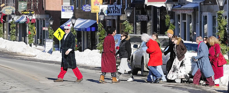 About 20 people dressed in pajamas and bathrobes or coats cross Water Street in downtown Hallowell on their way from an apartment, where they gathered on their way to a New Year's Day brunch at Slates Restaurant, on Tuesday. One of the organizers said that pajamas for brunch has been a holiday tradition for them for at least 10 years.