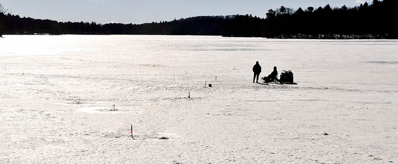A pair of fisherman wait for a flag to pop up on their ice fishing traps Thursday on Upper Pleasant Pond in Richmond.