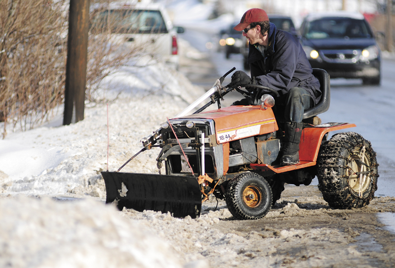 Andrew Nichols clears a driveway with a small plow on his garden tractor on Thursday in Hallowell. The storm the day before had dumped 3 to 4 inches of snow across the area.