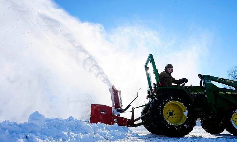 Justin Lord Willett, 12, runs a snowblower on the back of a farm tractor to clear a a work area on Tuesday in Hallowell.