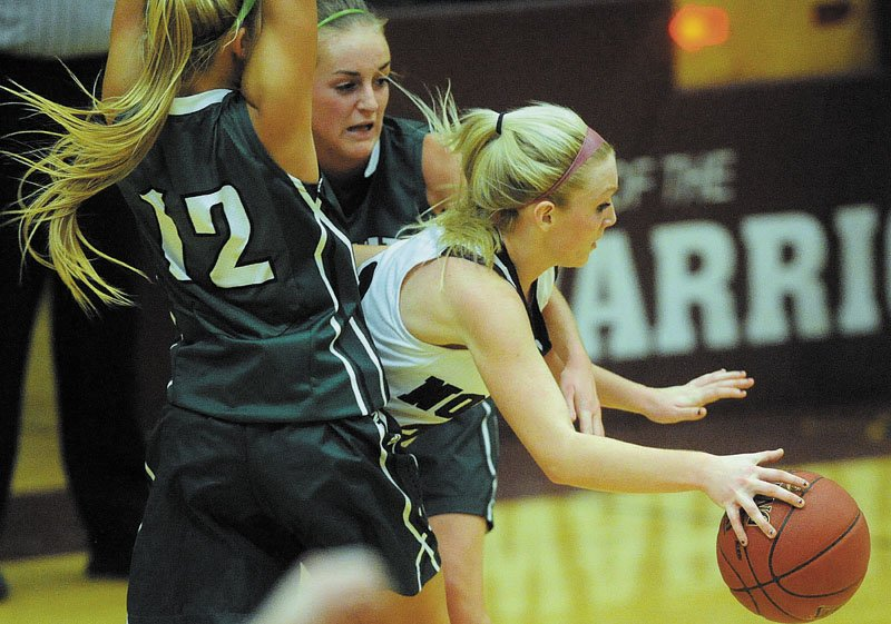 Nokomis High School's Lindsay Whitney, 22, splits Leavit tHigh School defenders, Mariah Treadwell, 12, and Jenna Cote, 11, in the third quarter in Newport Thursday.