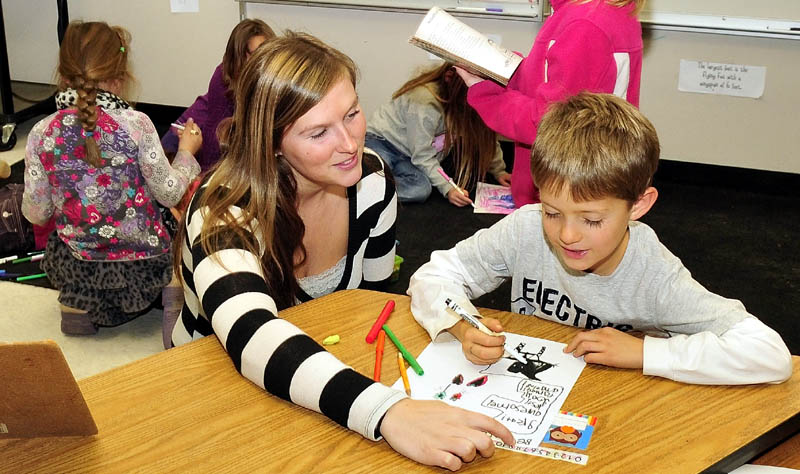 Cornville Regional Charter School teacher Danielle Beaman helps student Barret Walker recently. The school is accepting applications for 28 new student slots, and will accept those students via a lottery.