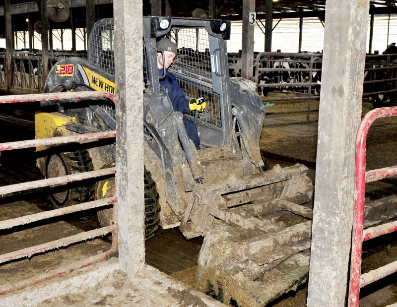 Stonyvale Farm worker Joachin Hershbine pushes cow manure into a transport system that takes the manure to a digester, where it is mixed with food waste. The gases produced are used to power an electric generator at the Exeter farm.