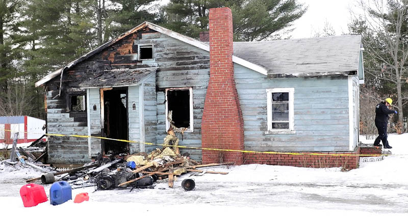 Mary MacMaster, an investigator with the State Fire Marshal's Office, exits the burned home of Al and Jenny Morales in Madison on Tuesday. Fire destroyed the home Monday evening.