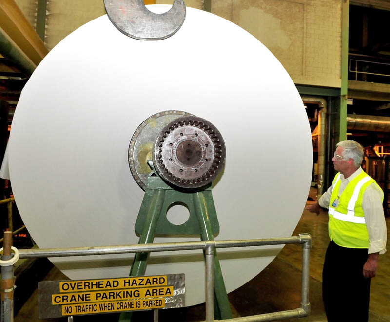 U.S. Rep. Mike Michaud examines a huge roll of finished paper made at the Madison Paper Industries mill in Madison, at the start of a statewide tour of mills, on Monday.
