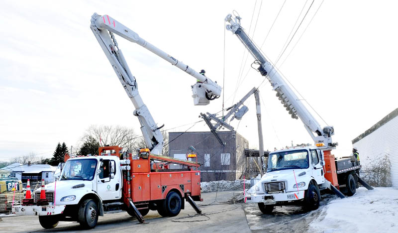 Central Maine Power Co. workers repair a broken pole behind the Fairfield municipal building on Monday. The pole, and another one behind the former Gerald Hotel, which is undergoing renovations, caused a power outage to 1,103 area customers.