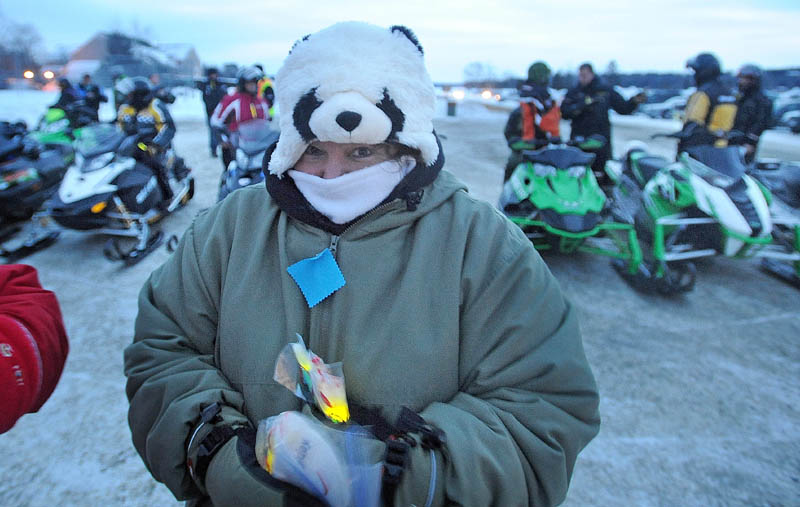 Leslie Walton hands out glow sticks before the Torch Light Snowmobile Safety Vigil in Rangeley on Friday night. The vigil was geared toward snowmobile safety awareness.