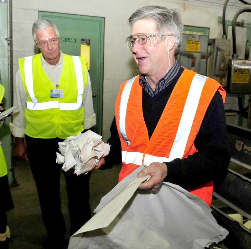Madison Paper Industries President and CEO Russ Drechsel, right, shows grades of paper from a finished roll made at the Madison mill during a tour for Congressman Mike Michaud, left, on Monday.