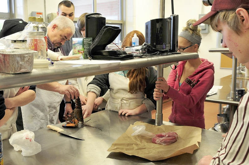 Regional School Unit 9 culinary arts teacher Sean Minear shows students how to prepare a lobster, in a crowded room at Mt. Blue High School Learning Campus in Farmington recently. More space will become available for the program when the three-year expansion project is finished later this year.