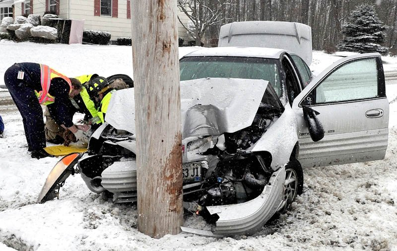 A female occupant of this vehicle is treated by ambulance personnel after the vehicle slid off snow covered Chase Avenue in Waterville and struck a utility pole on Wednesday.
