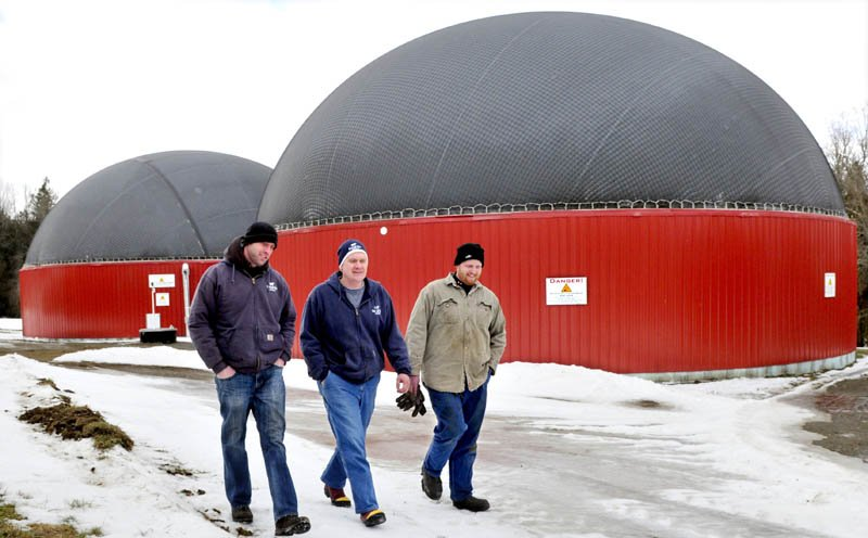 Adam Wintle, left, Travis Fogler and John Wintle walk past the two digester buildings, where food waste and cow manure are mixed to produce gas that powers a generator for electricity, at Stonyvale Farm in Exeter.