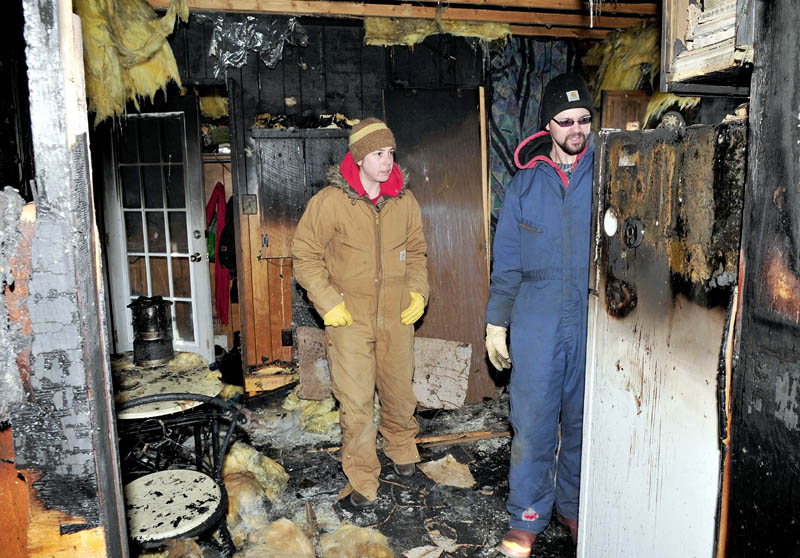 Kim Ricciardelli, left, and Bryan Cocchio search for salvageable photos inside the kitchen of their mobile home on Thursday. Fire destroyed the uninsured home Wednesday evening. Cocchio believes the fire may have started near some heat tape.