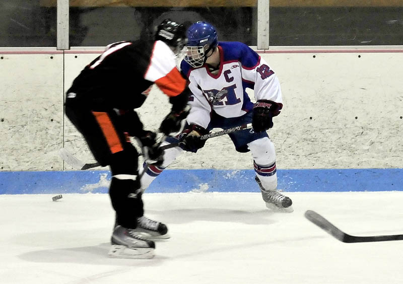 CHASE IT DOWN: Messalonskee's Chase Cunningham (12) battles for the puck against Brewer on Wednesday at Sukee Arena in Winslow.