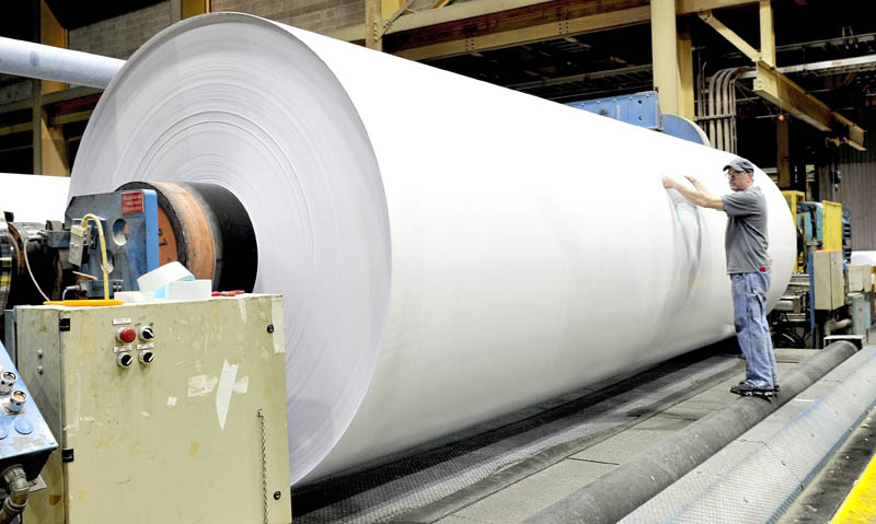 Sappi Fine paper worker Jeff Lancaster works on a huge roll of coated paper that will be cut into smaller rolls at the Skowhegan mill on Thursday.