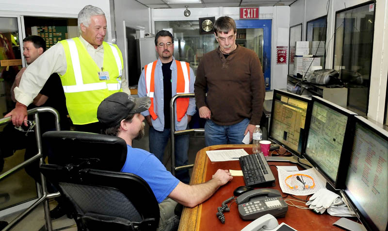 U.S. Rep. Mike Michaud, left, listens to Jeremy Vigue, seated in a paper machine control room, at the Madison Paper Industries mill, during a tour on Monday. Standing are, from left, employee Troy Bonnevie, Michaud, and employees Mike Croteau and Craig Hunnewell.