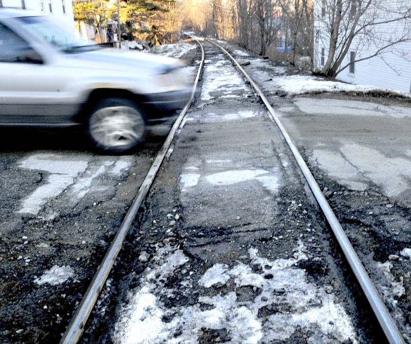 A motorist drives over a rough railroad crossing on Elm Street in Fairfield on Monday. The Town Council is considering closing the crossing, and possibly another, to qualify for grant money which could be used to repair other crossings in town.