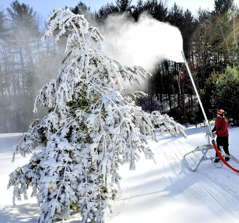 Tim Norton of J.R. Fabrication Co. makes adjustments to some of the new snow-making equipment on trails at the Quarry Road Recreation Area in Waterville Monday.