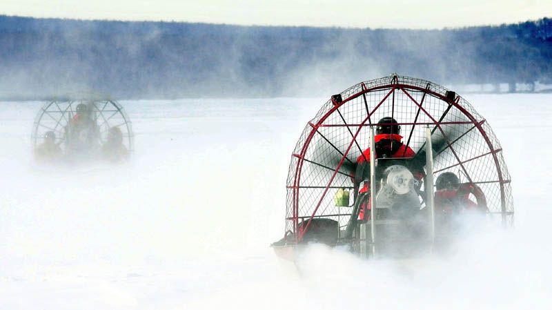 Two Maine Warden Service air boats head out on the ice on Rangeley Lake in Rangeley last week, to the open-water location where four snowmobiles went through the ice on Dec. 30. One body has been recovered and three other riders are presumed drowned. Harsh weather and poor ice conditions have impeded recovery efforts.