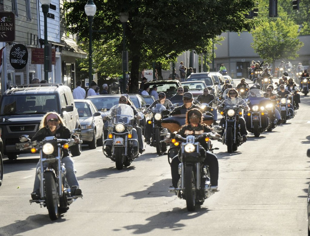 A motorcycle parade thunders down Water Street in Gardiner in this 2010 photo. Current law requires only motorcyclists under 18 years old to wear a helmet when driving or riding as a passenger.