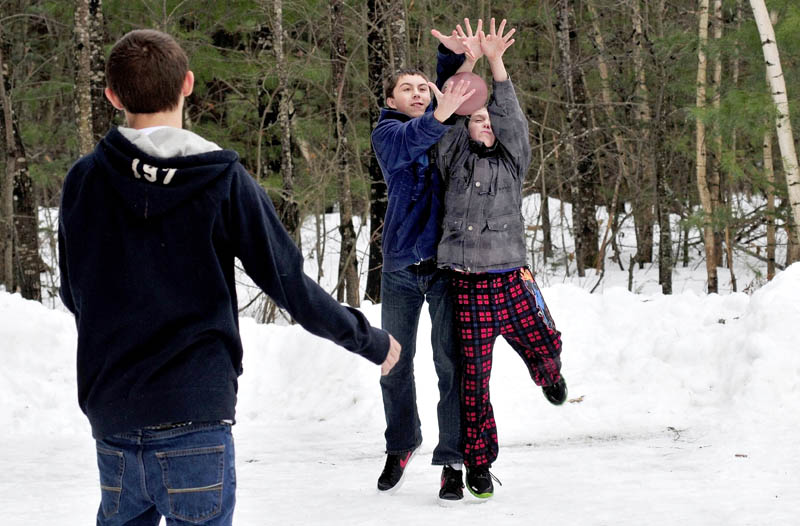 Caleb Latham, left, watches as Tylor Latham, center, and Deven Boyker reach for a football, in Farmington on Sunday. The mild temperatures melted snow and ice and allowed the boys to have a game of catch.