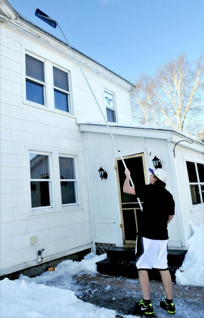 """It may have been freezing outside, but not enough for Cameron Aucion to wear long pants while using a roof rake to knock down icicles off a home in Waterville on Wednesday. """"I don't think its really cold anyway, """" Aucion said."""