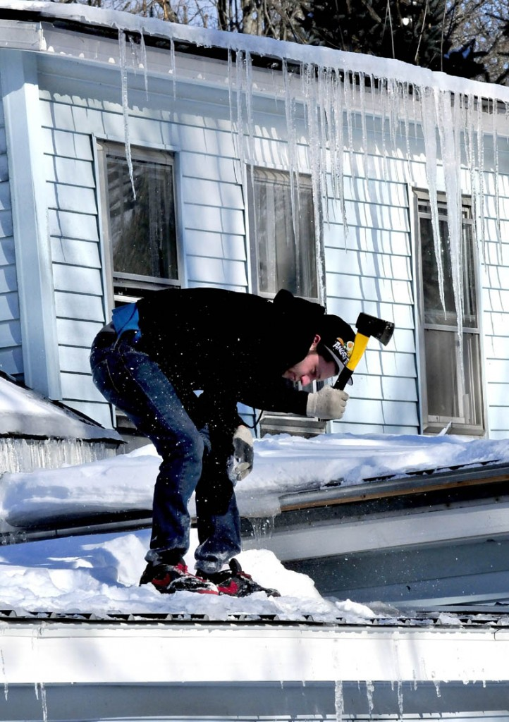 Josh Mosher uses an axe to break up ice that froze on a roof at his home on Lincoln Street in Waterville on a chilly Wednesday.