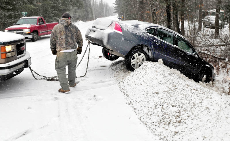 Todd Stanton backs up after attaching a chain to a vehicle that slid off Route 137 and landed in a snowbank on Hanscom Road in Benton on Wednesday.