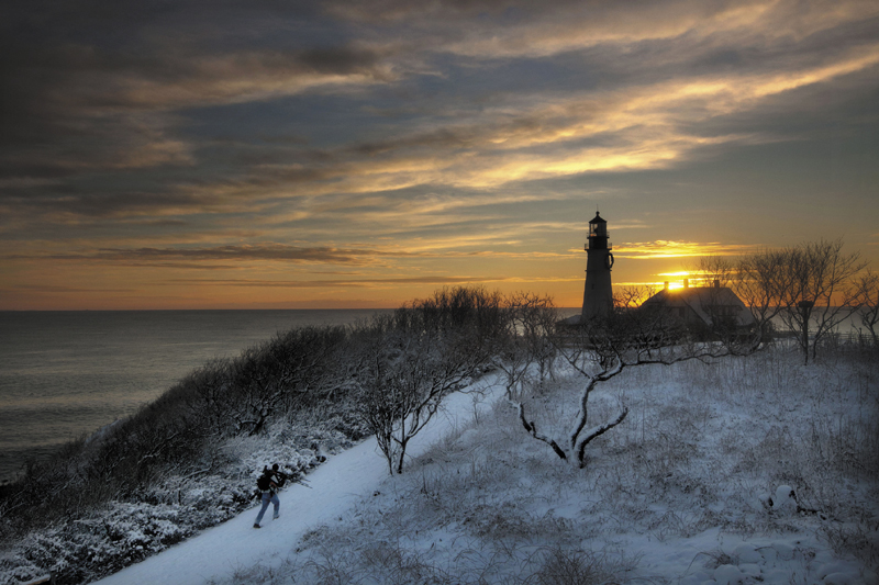 Clearing skies await a tripod-toting photographer looking for a spot to capture the early-morning light at Portland Head Light Thursday, in Cape Elizabeth. A snowstorm that ended before dawn temporarily transformed Fort Williams Park into a snowy scene.