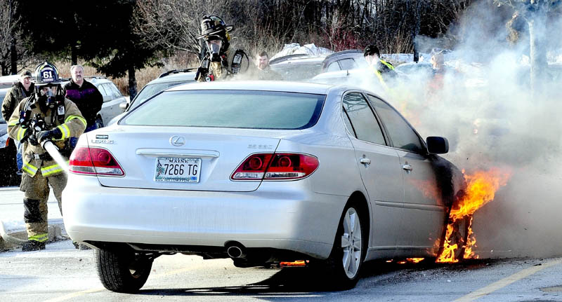 """Waterville firefighters extinguish a fire that destroyed a 2005 Lexus sedan parked at Marden's Surplus and Salvage, at 458 Kennedy Memorial Drive in Waterville, on Monday. Owner Lucille Roberge of Waterville said the car, which she recently purchased, was insured. """"I came out of the store from shopping and said to myself that someone's car was on fire, before I realized it was mine,"""" Roberge said. """"I loved that car."""""""