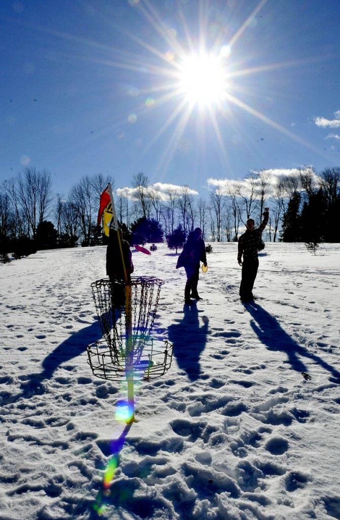 Staff photo by David Leaming JANUARY THAW: Dalton McGovern, right, throws his hand in the air in hopeful anticipation as the disc he threw heads for the basket while playing disc golf at the Quaker Hill Farm in Fairfield on an unseasonably warm day on Thursday, Jan. 10, 2013. Also playing and enjoying the sunny day are Josh Newhall, left, and his cousin Sean Newhall.