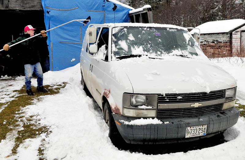 Larry Andersen uses a roof rake to reach the snow that has accumulated on his van in Cornville on Thursday, Jan. 17. 2013.
