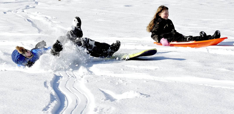 Madia Chesner, right, finished her sled ride in style while friend Ricky Hallowell came to an abrupt end while sledding with family at the Pinnacle in Pittsfield on Thursday, Jan. 17, 2013.