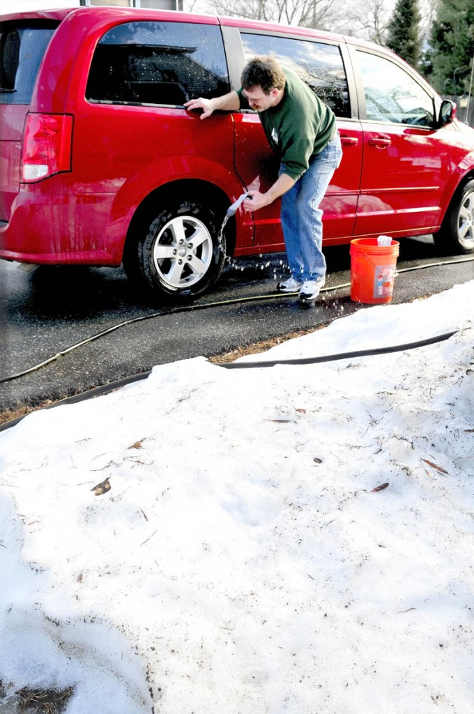 """Tom McCormick washes his van in Waterville as temperatures rose above 50 degrees on Monday. """"I don't mind this weather; at least you don't have to shovel humidity,"""" McCormick said."""