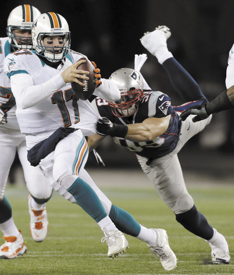BIG EFFORT: Defensive end Trevor Scott (99) tries to tackle Miami Dolphins quarterback Ryan Tannehill (17) during the third quarter of the Patriots' 28-0 win Sunday in Foxborough, Mass. Gillette Stadium