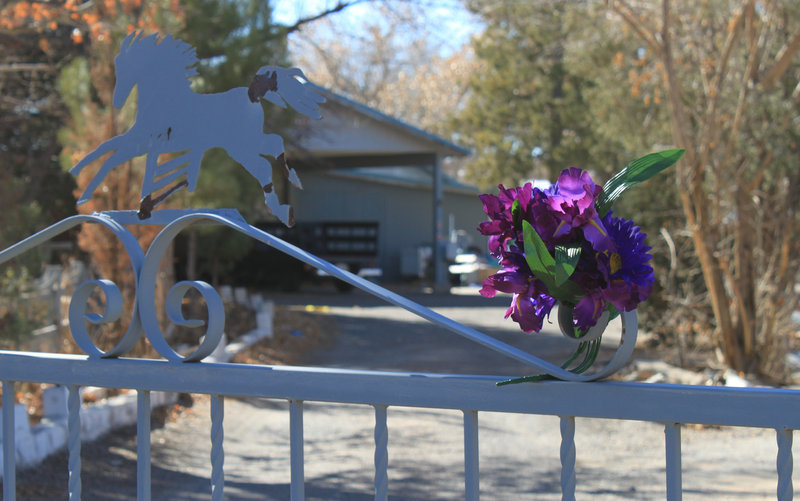 A bouquet adorns the gate Monday at the home where a couple and their three young children were found shot to death south of Albuquerque, N.M., over the weekend.