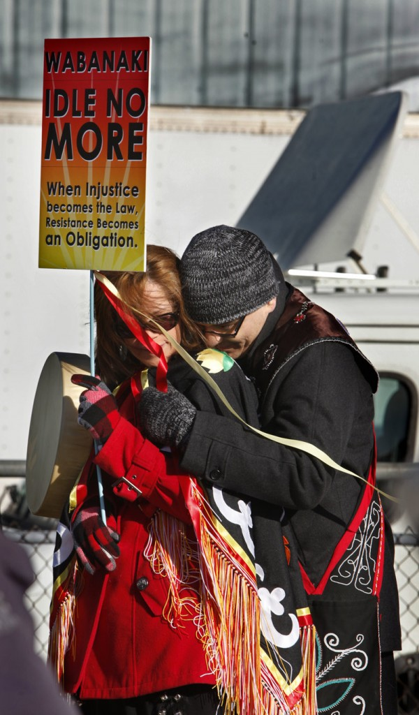 Donna Brown, left, and her husband, Jason, huddle against the wind while listening to speakers at the anti-tar sands rally Saturday.