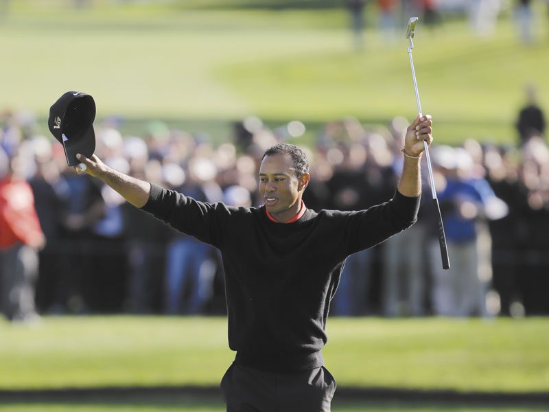 BACK ON TOP: Tiger Woods celebrates after winning the Farmers Insurance Open on Monday in San Diego. Woods closed with an even-par 72 for a four-shot victory.