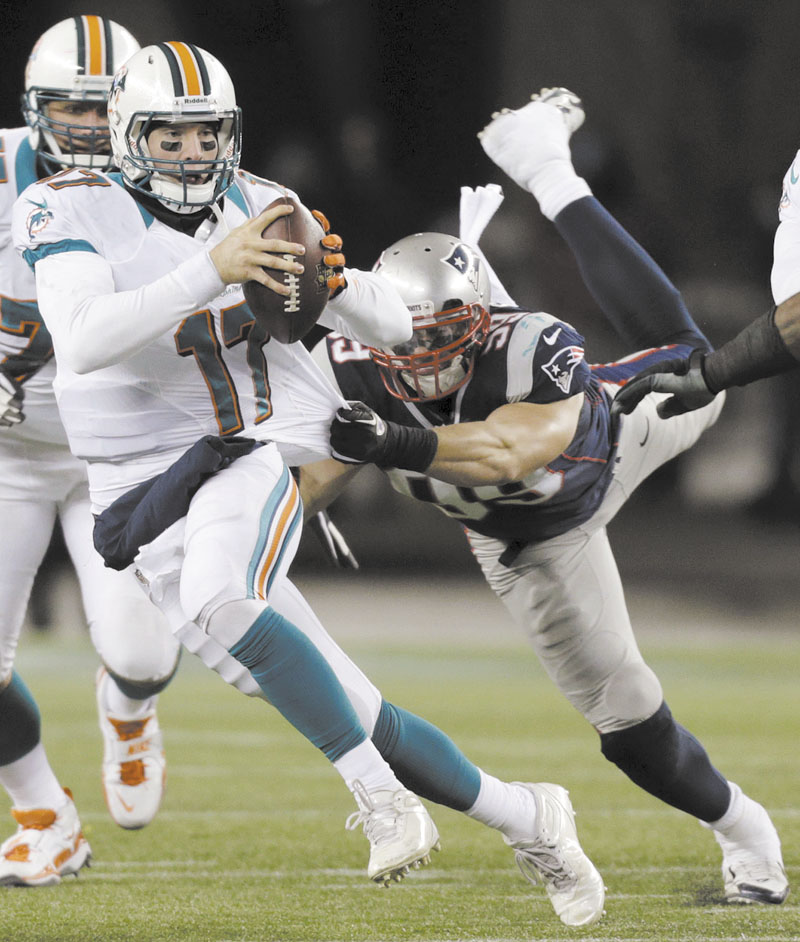 New England Patriots defensive end Trevor Scott (99) tries to tackle Miami Dolphins quarterback Ryan Tannehill (17) earlier this season. Scott will make his playoff debut Sunday. Gillette Stadium