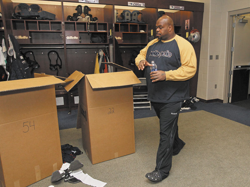 PACKING UP: New England Patriots defensive tackle Vince Wilfork walks past boxes of gear in the locker room Monday at Gillette Stadium in Foxborough, Mass. The Patriots wrap up their season after Sunday's night's loss to the Baltimore Ravens in the AFC Championship game.