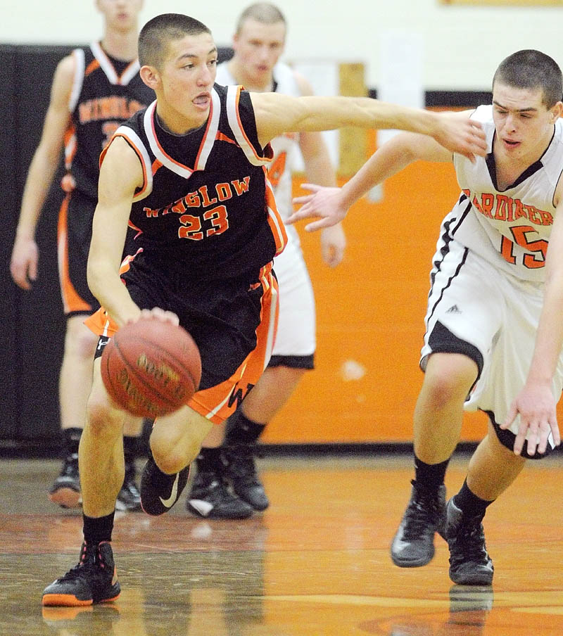 PASS ON BY: Winslow's Nason Lanphier, left, is covered by Gardiner's Jensen Orewiler on Saturday at the John A. Bragoli Memorial Gym in Gardiner. Winslow won the game 58-48.