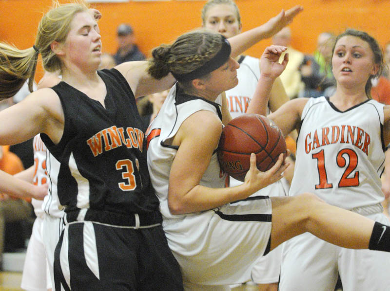 Winslow's Megan Richards, left, Gardiner's Ally Day along teammate Taylor Banister go up for a rebound during a game on Saturday at the John A. Bragoli Memorial Gym in Gardiner.