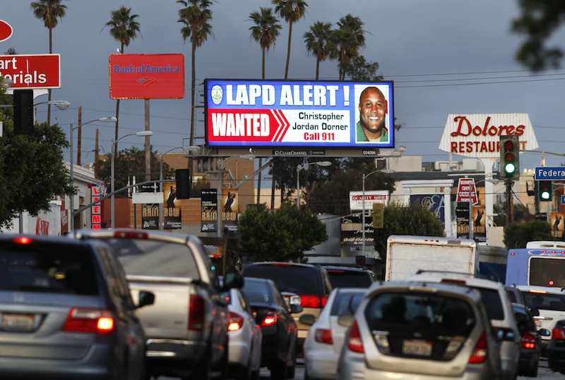 """A digital billboard along Santa Monica Boulevard on the west side of Los Angeles shows a """"wanted"""" alert for former Los Angeles police officer Christopher Dorner Friday, Feb. 8, 2013. Dorner is suspected in a spree of violence as part of a vendetta against law enforcement after being fired by the department. He is also a suspect in the shooting deaths of a former LAPD captain's daughter and her fiance, and two other shootings that left an officer dead and two others wounded. (AP Photo/Reed Saxon)"""