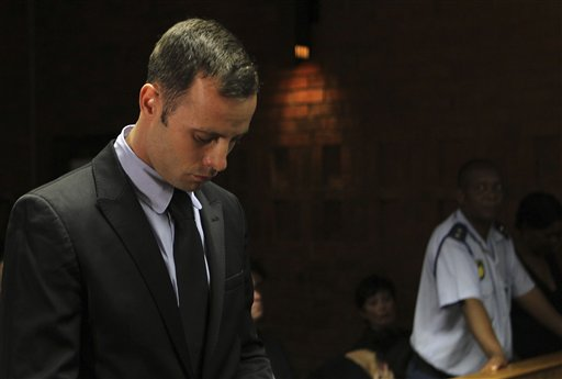 "Olympic athlete Oscar Pistorius stands inside the court as a police officer looks on during his bail hearing at the magistrate court in Pretoria, South Africa, on Wednesday. A South African judge says defense lawyers will need to offer ""exceptional"" reasons to convince him to grant bail for Pistorius."