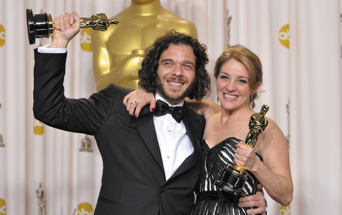 "Sean Fine, left, and Andrea Nix Fine pose with their award for best documentary short subject for ""Inocente"" during the Oscars at the Dolby Theatre on Sunday."