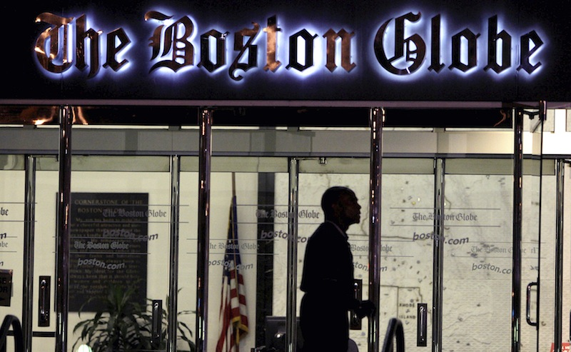 In this July 20, 2009 file photo, a security guard walks past the entrance of The Boston Globe building in the Dorchester neighborhood of Boston. The New York Times Company, which owns The Globe, announced Wednesday, Feb. 20, 2013, that it has put The Globe up for sale. (AP Photo/Charles Krupa)