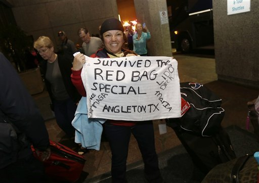 Veronica Arriaga, of Angleton, Texas, a passenger from the disabled Carnival Triumph cruise ship, holds a sign referring to the red biohazard bags used as toilets, as she arrives at the Hilton Riverside Hotel in New Orleans on Friday.