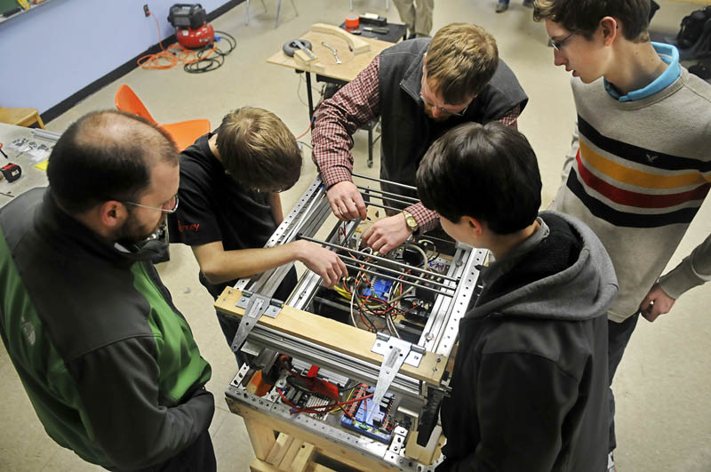 Members of the Gardiner Area High School robotics team wire the robot they are building Thursday at the high school. The completed robot will launch Frisbees into goals while being operated remotely, at an April competition.