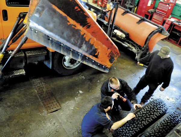 Augusta Public Works mechanics Jason Arbour, left, and Rick Merrill inspect plow tires with shop foreman Shawn Harrington, Monday, at the city's garage.