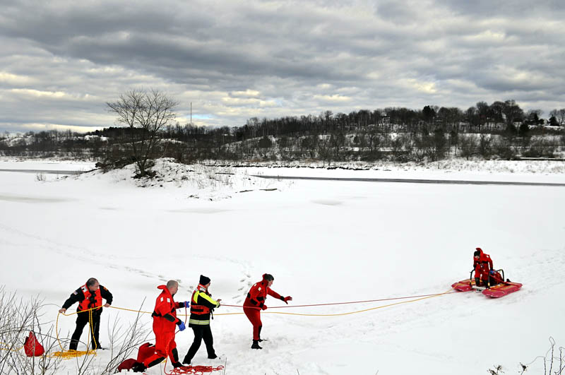 Augusta firefighters tow colleagues off the Kennebec River Tuesday in Augusta, during the department's annual ice rescue training. The firefighters practice retrieving either an injured or stranded person trapped on the ice with dry suits and a floating sled, according to Battalion Chief Scott Dunbar.